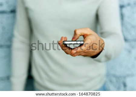 Closeup image of a male hand holding smartphone - stock photo
