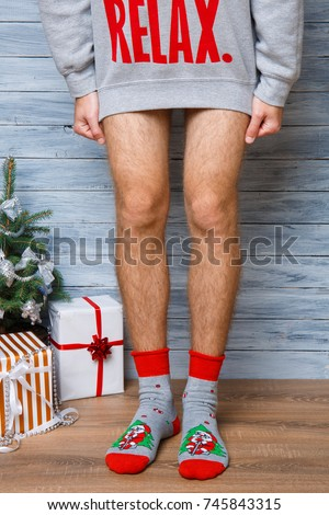 Closeup image of a man who is standing in a long sweater without pants in New Year's socks.