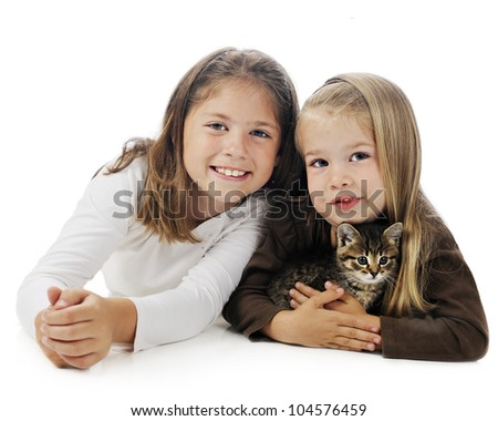 Closeup image of a pretty elementary girl and her adorable preschool sister holding a young kitten.  On a white background.