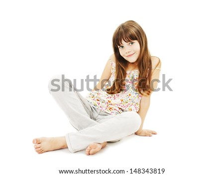 Closeup image of a pretty little girl sitting on the floor in jeans. Isolated on white background  - stock photo