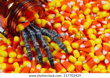 Closeup image of a scary hand coming out of jar into pile of candy corn - stock photo