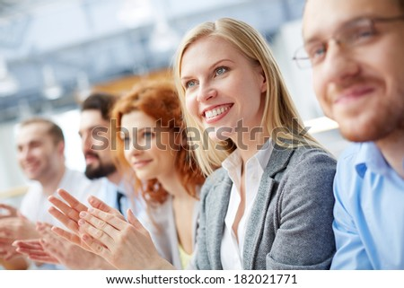 Closeup image of a smiley business leader clapping at the seminar with her team on the foreground  - stock photo