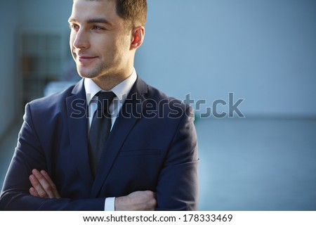 Closeup image of a smiling businessman on the foreground  - stock photo
