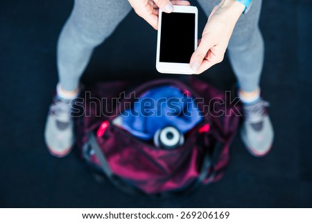 Closeup image of a sports woman holding smartphone - stock photo