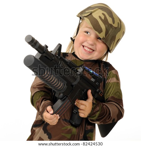 """Closeup image of a tiny girl """"soldier"""" delightedly firing a toy machine gun.  Isolated. - stock photo"""