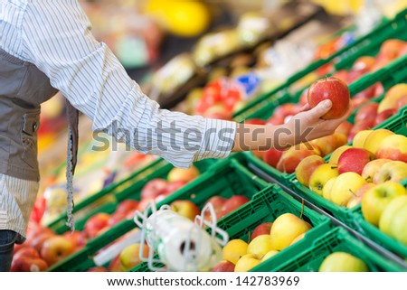Closeup image of a woman selecting apples from the food counter at the supermarket. - stock photo