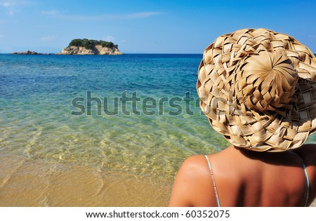 Closeup image of a young woman in a straw hat and bikini, looking at a tiny island in the Mediterranean