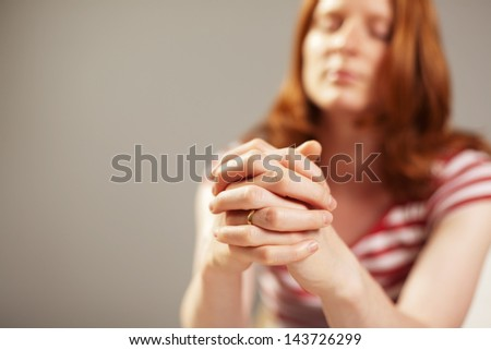 Closeup image of a young woman praying, focus on her hands. - stock photo