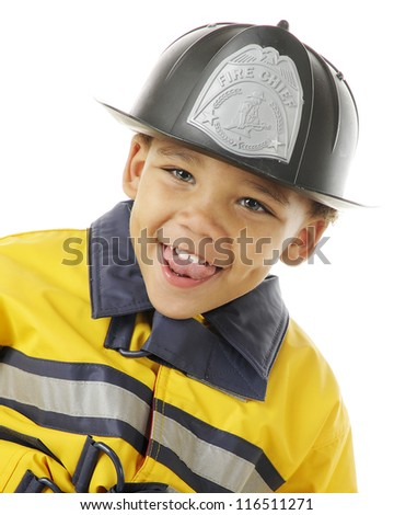 "Closeup image of an adorable preschool ""Fire Chief"" in his helmet and yellow coat.  On a white background. - stock photo"