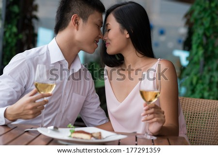 Closeup image of an amorous couple on a date being about to kiss on the foreground  - stock photo