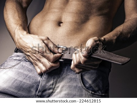 Closeup image of attractive young muscle man undoing belt, shirtless fashion male portrait wearing jeans, contrast studio, grunge fashion male portrait  - stock photo