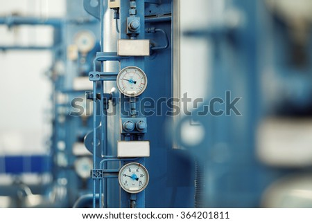 Closeup image of barometers at a brewery industrial plant.