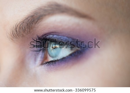 Closeup image of beautiful woman eye with fashion purple makeup