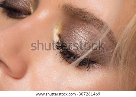 Closeup image of beautiful woman eye with makeup looking down