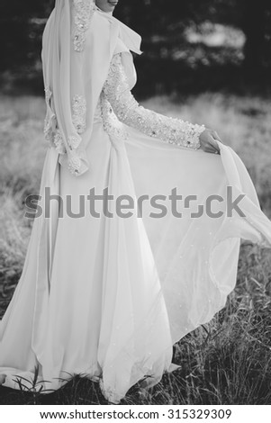 Closeup image of black and white half length body portrait of women or bride hold beautiful wedding dress on outdoor background location, military and officer wedding - stock photo