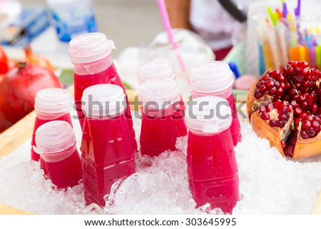 Closeup image of bottles of fresh pomegranate juice on ice for sell. - stock photo