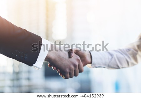 Closeup image of business partners making handshake outdoors, modern office or skyscrapers on the background, flare light - stock photo