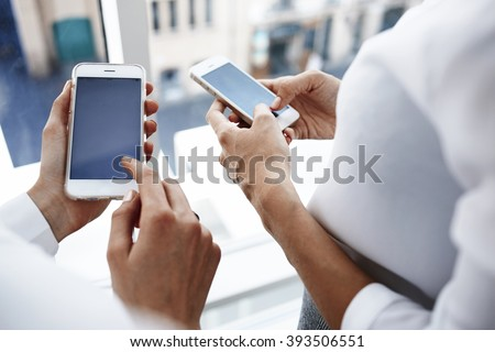 Closeup image of businesswoman pointing the finger on a copy space on the screen mobile phone for your advertising text message or promotional content, while her secretary near is using cell telephone - stock photo
