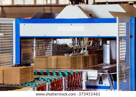Closeup image of cardboard boxes on conveyor belt in distribution warehouse - stock photo
