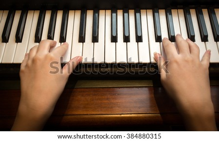 Closeup image of child's hands playing on the piano - stock photo