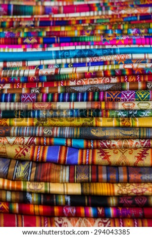 Closeup image of classical colorful Peruvian and Bolvian clothes and handicraft at the indigenous market in Otavalo. Ecuador 2015. - stock photo