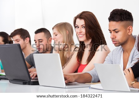 Closeup image of college students using laptops at desk - stock photo