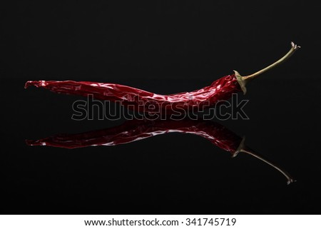 Closeup image of dried red hot chili pepper on black background with reflection - stock photo