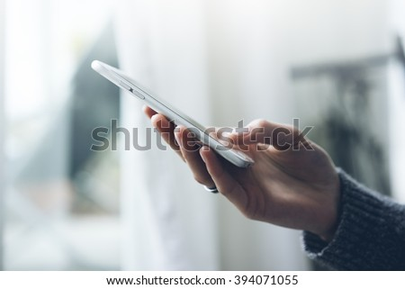 Closeup image of female hand using cellphone in interior, woman'??s hand typing on smartphone text message while working at office