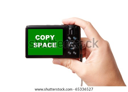 Closeup image of hand, holding modern compact digital photo camera, isolated on white background, with easy to cut-out green display - copy space for your picture or text - stock photo