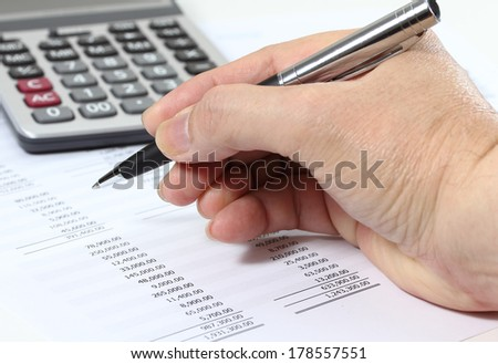 closeup image of hand holding pen and calculator on business graph report for working
