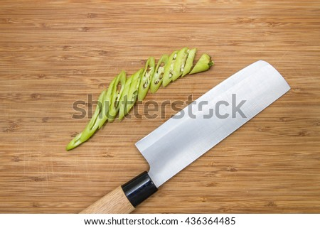Closeup image of kitchen japanese style chef knife and green hot chilli chopped on vintage cutting board - stock photo