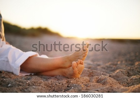 Closeup image of legs of senior woman sitting relaxed on sandy beach. - stock photo