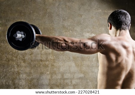 Closeup image of man lifting dumbbells in front of dirty wall background at old gym.