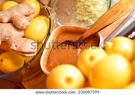 closeup image of organic healthy food ingredients as lemon, honey, ginger & wooden spoon - stock photo