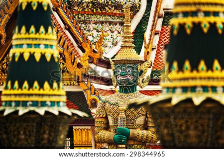 Closeup image of ravana giant statue from Wat Phra Kaew, Bangkok, Thailand at color palace roofs background. - stock photo