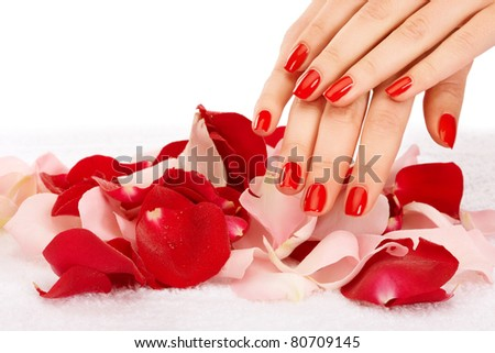 Closeup image of red manicure with leafs of rose - stock photo