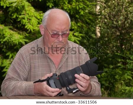 closeup image of senior adjusting a zoom lens onto dslr - stock photo