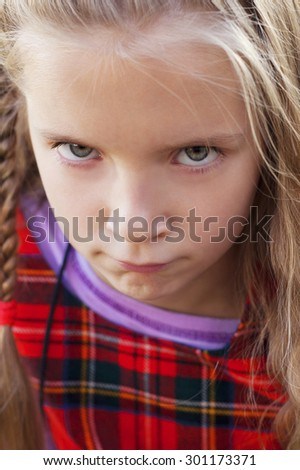 closeup image of the cute emotional frowning little girl outdoors