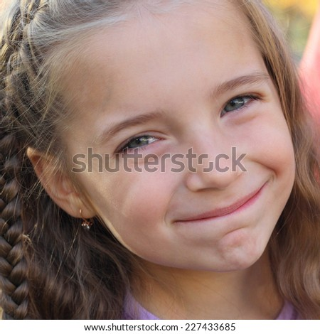 closeup image of the cute emotional smiling little girl in the park
