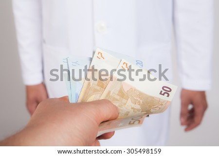 Closeup image of the patient paying to the doctor - stock photo