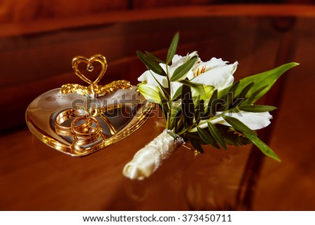 Closeup image of wedding rings and white flowers boutonniere at brown table background. - stock photo