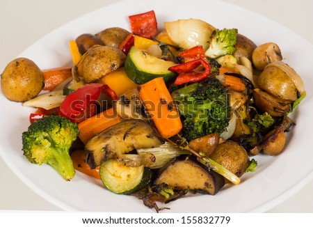 Closeup image of white dinner plate with with different healthy vegetables. like  mushroom gravy, potatoes, red pepper, carrots, red beet, fennel, onions, green beans,zucchini, broccoli and garnish.