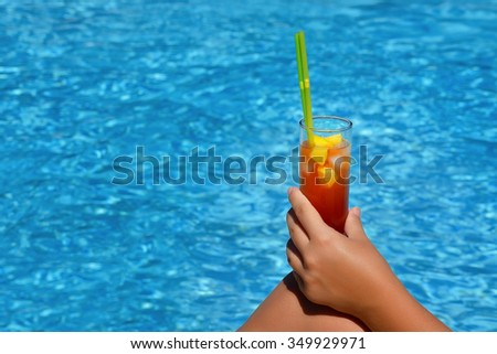 Closeup image of woman hand holding cocktail at swimming pool