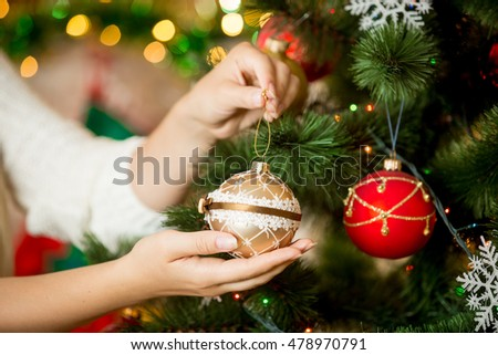 Closeup image of woman in sweater decorating Christmas tree with baubles