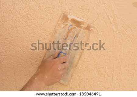 Closeup image of worker hand spreading colored mortar over styrofoam insulation with trowel  - stock photo