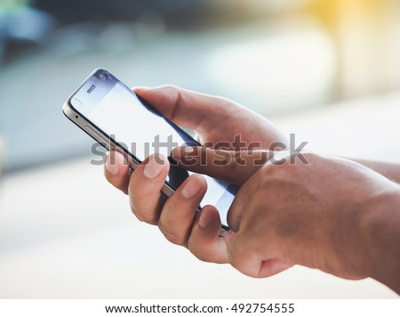 Closeup image on a male hands using smartphone.