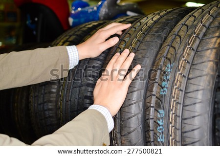 Closeup image on hands choosing a car tire or tyre - stock photo