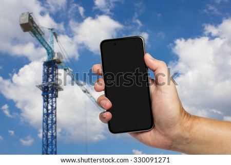 Closeup image with male hand hold and touch screen smart phone, tablet,cellphone over blurred Construction site background. - stock photo
