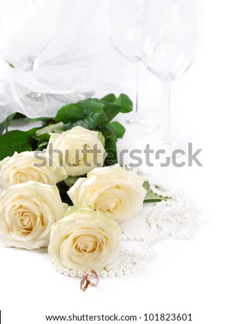 Closeup image with white roses, bridal rings and vine goblets - stock photo