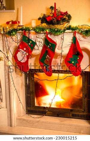 Closeup interior photo of three Christmas stockings hanging on decorated fireplace - stock photo